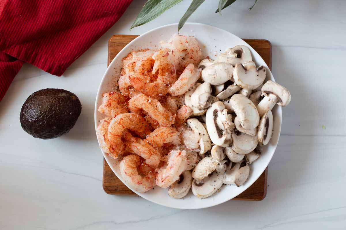 Shrimp and sliced mushrooms on a plate and seasoned to make Mexican Shrimp Tacos.