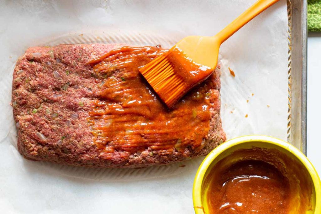 basting a meatloaf with glaze before baking