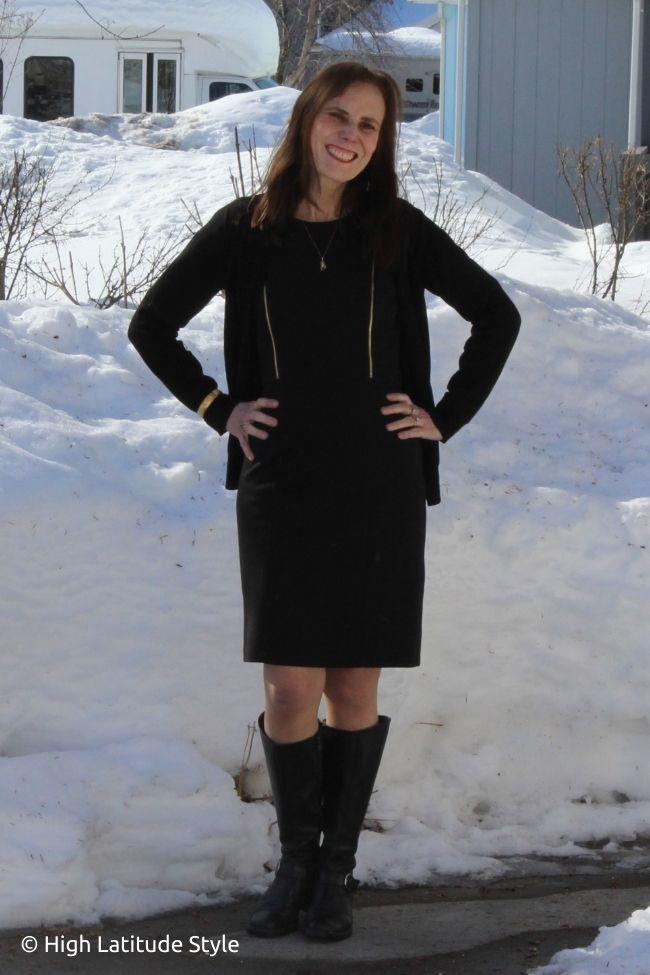 fashion blogger in black sleek tailored dress, fine knit cardigan, pantyhose, boots, bangle, pendant necklace, studs