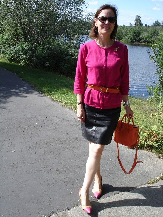 midlife fashion blogger in casual work look with leather skirt, pink top and orange belt and bag