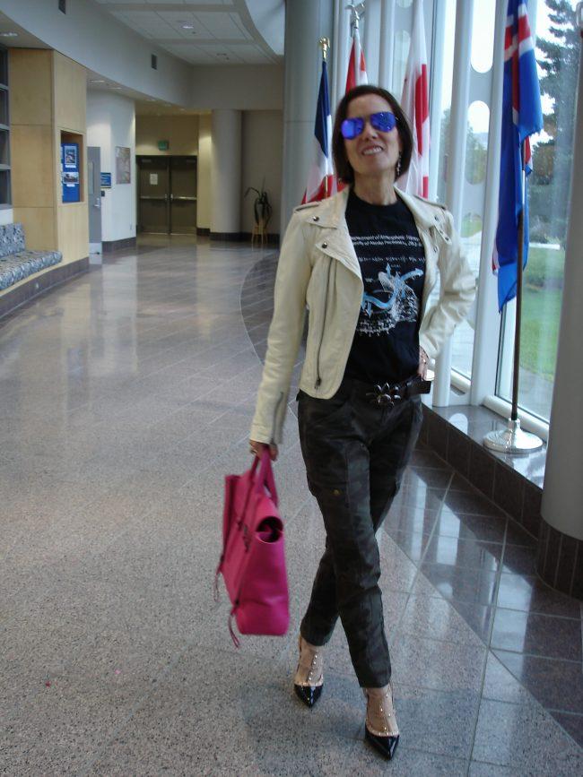 stylist in white motorcycle jacket, printed pants, pumps pink bag
