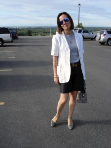 over 50 years old fashion blogger in desaturated work attire with short leater pants and blazer
