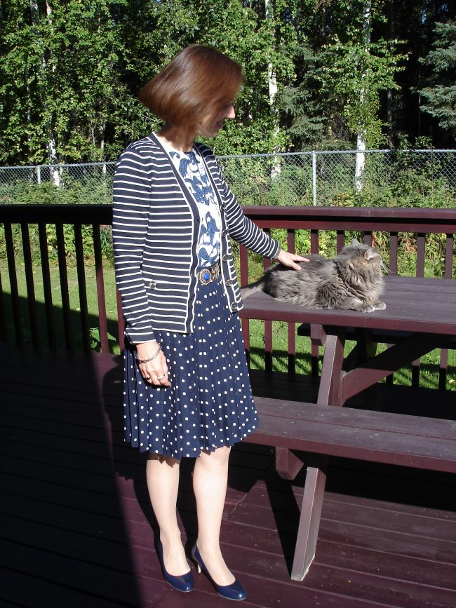 stylist in two cardigans, pleated polka dot summer skirt styled for fall