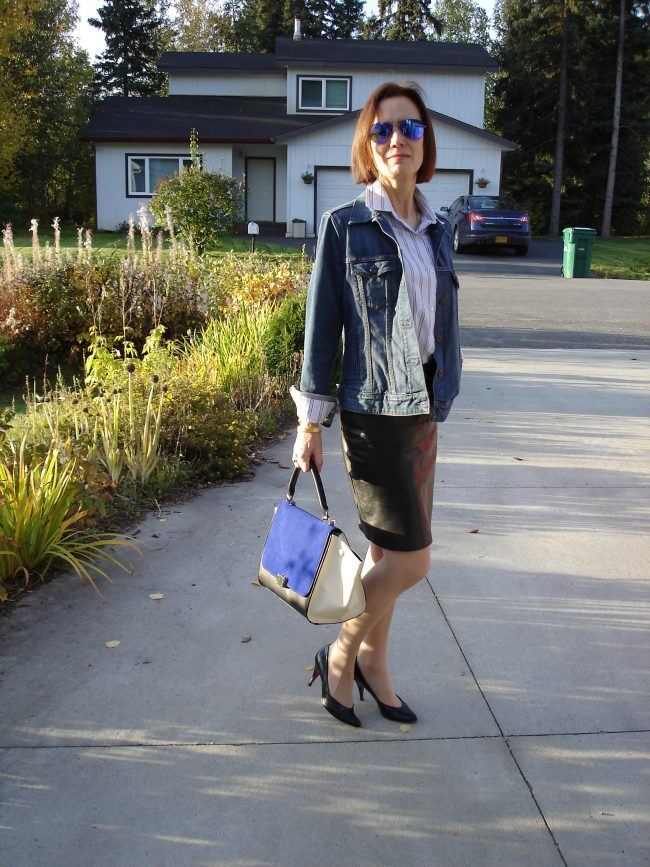style blogger in black leather pencil skirt, oversize denim jacket and white blue striped button-down shirt