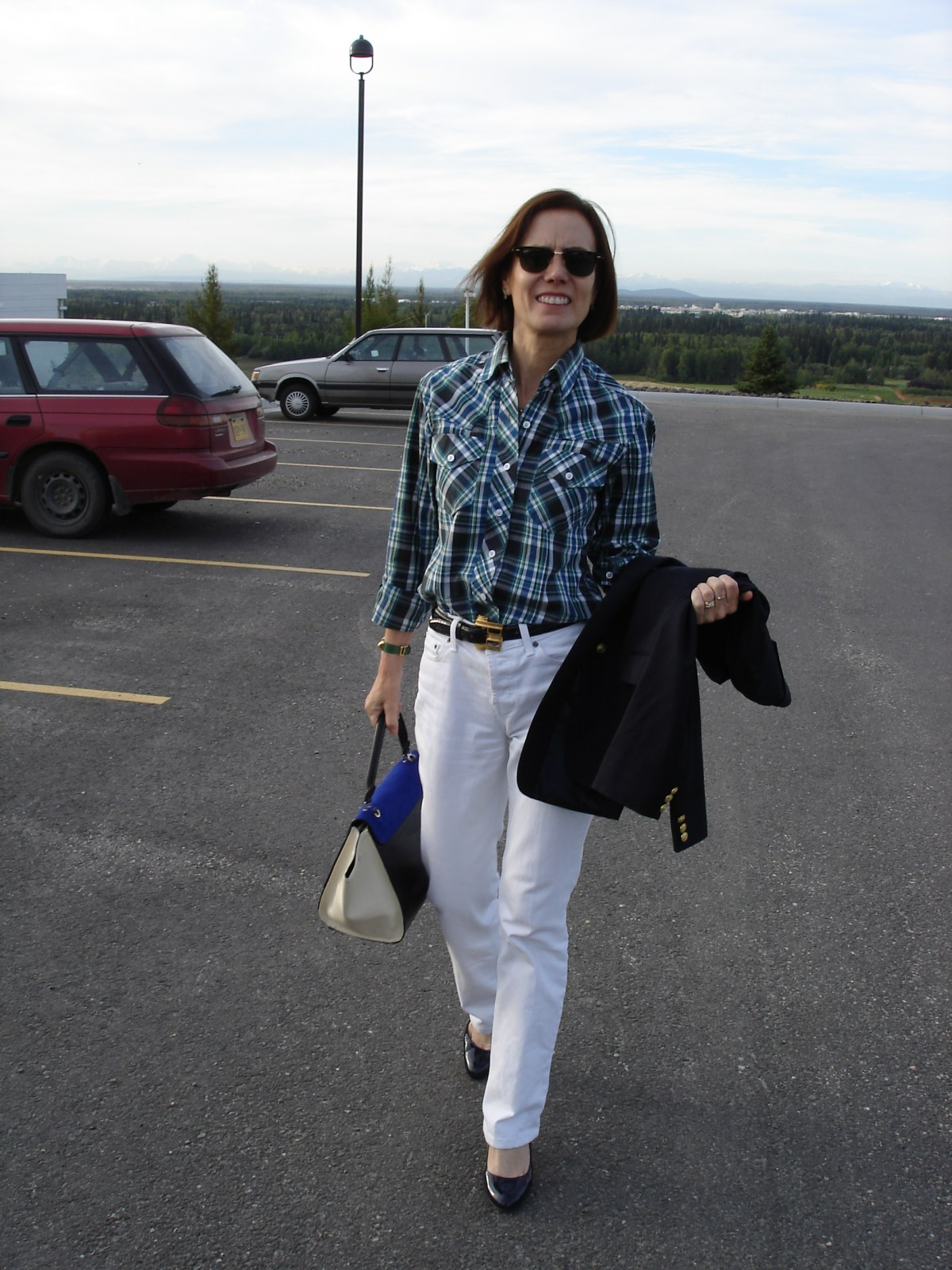 midlife woman in boyfriend jeans with navy blazer, plaid shirt, and pumps