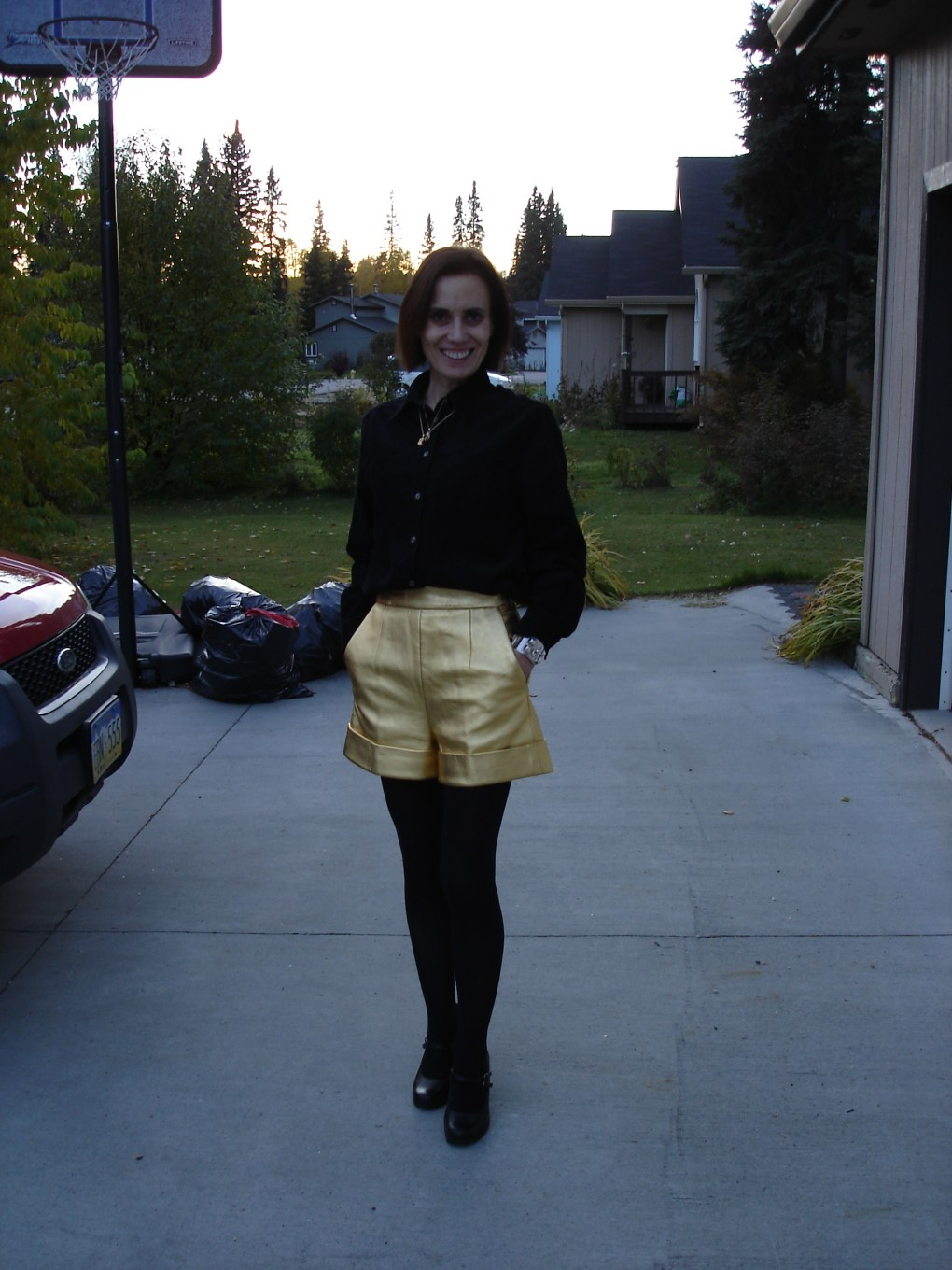 midlife woman in gold leather shorts