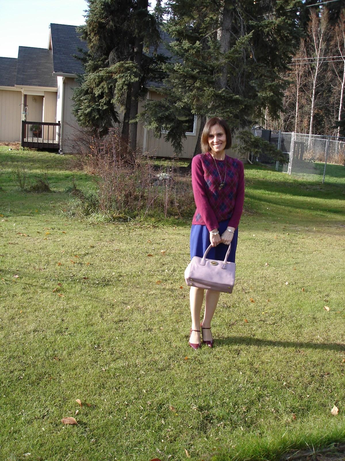 Nicole of High Latitude Style wearing a argyle sweater over a sheath dress