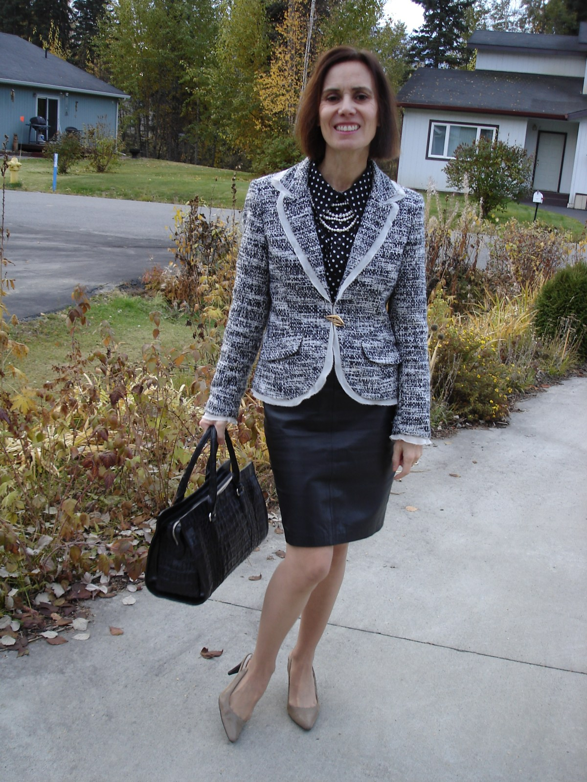 mature fashion blogger in black leather skirt and pepper and salt blazer
