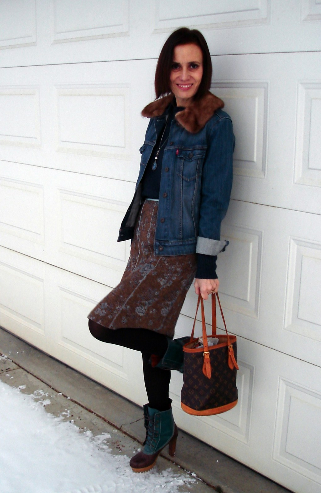 over 50 fashion mature woman wearing a tweed skirt with denim jacket