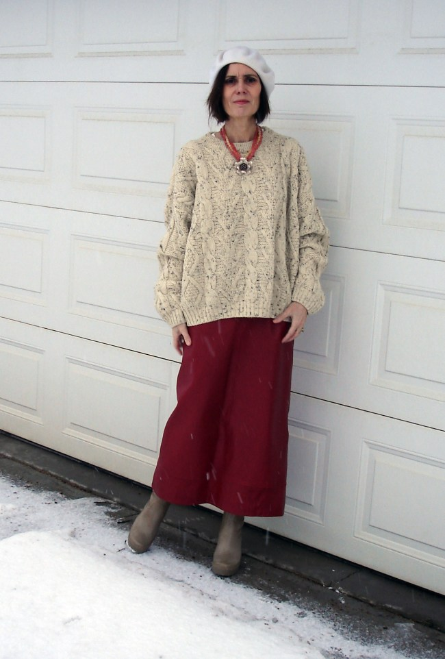 fashion blogger over 50 wearing a long leather skirt with oversized sweater