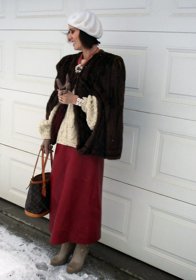 fashion blogger over 50 in cable knit sweater with long leather skirt