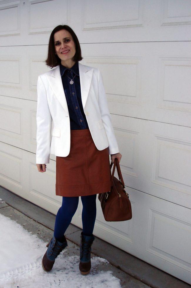 European older woman in tan leather skirt, blue shirt white blazer