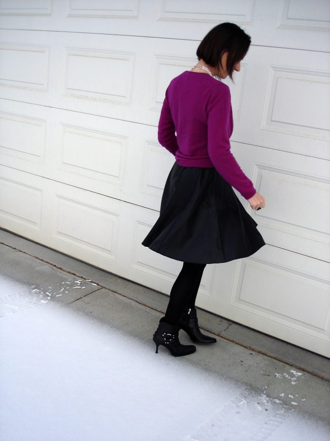 trendsetter in leather dress with fuchsia cardigan, tights, booties