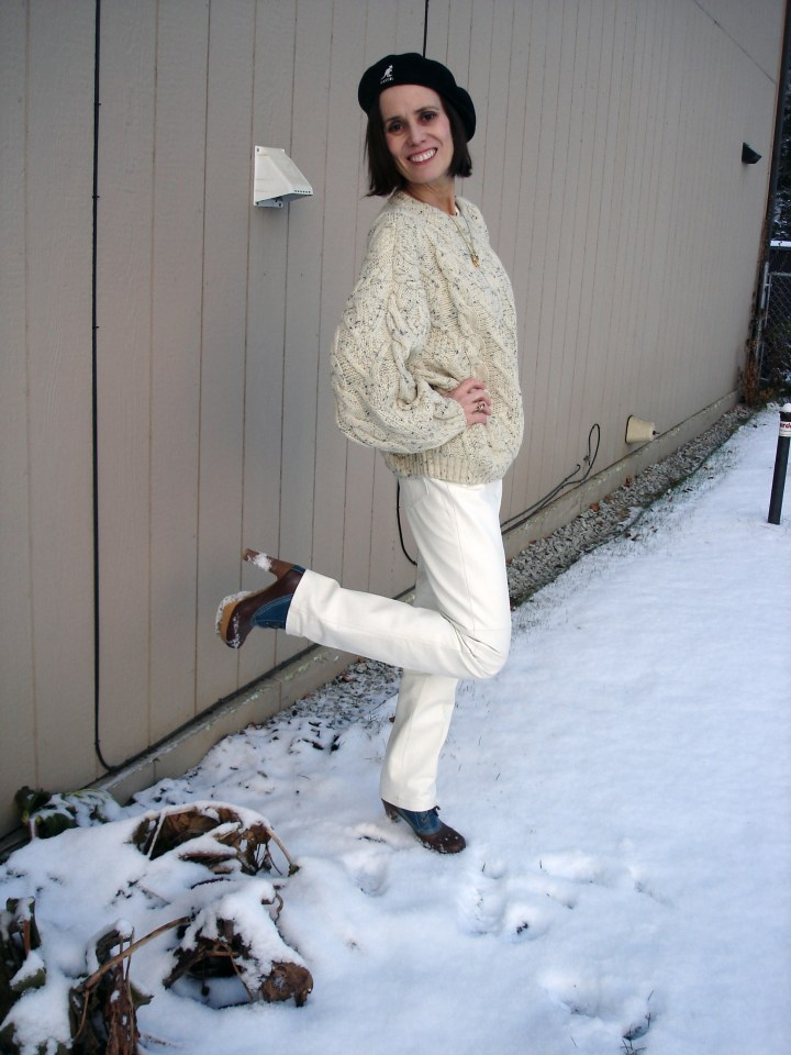 fashion blogger over 50 in white leather pants with Irish cable knit sweater