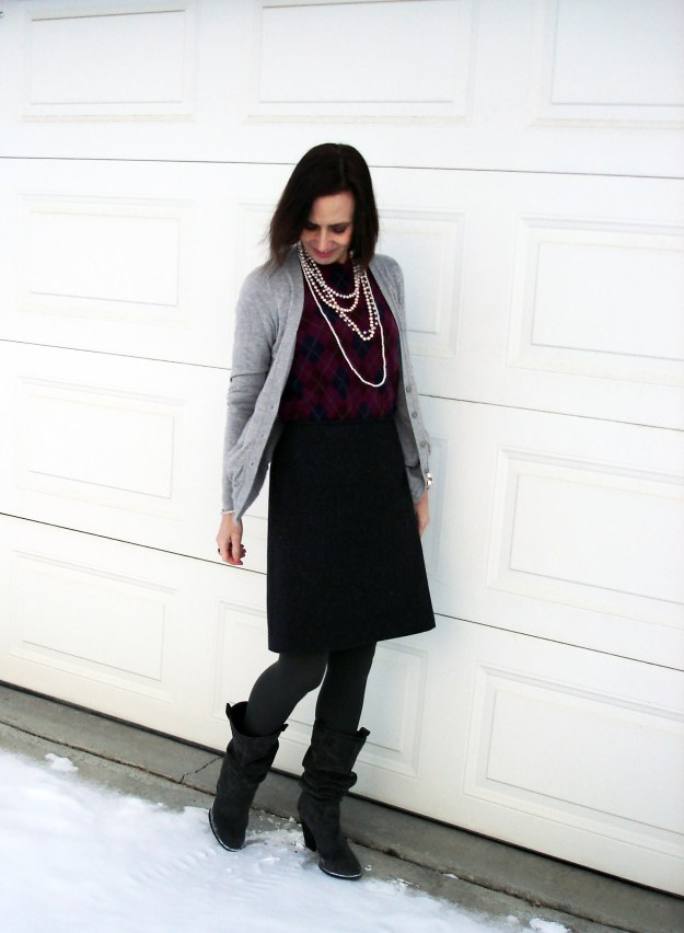 Classic winter work outfit ith sweater, cardigan, tweed skirt, tights, boots and pearls