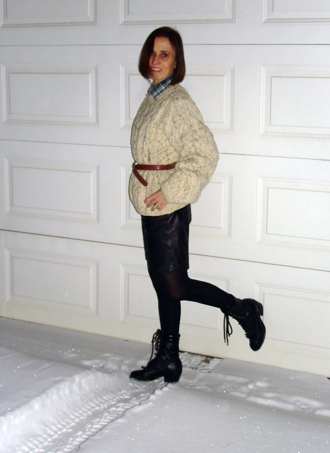influencer in oversize cableknit sweater, leather bermudas, tights, belt booties and shirt