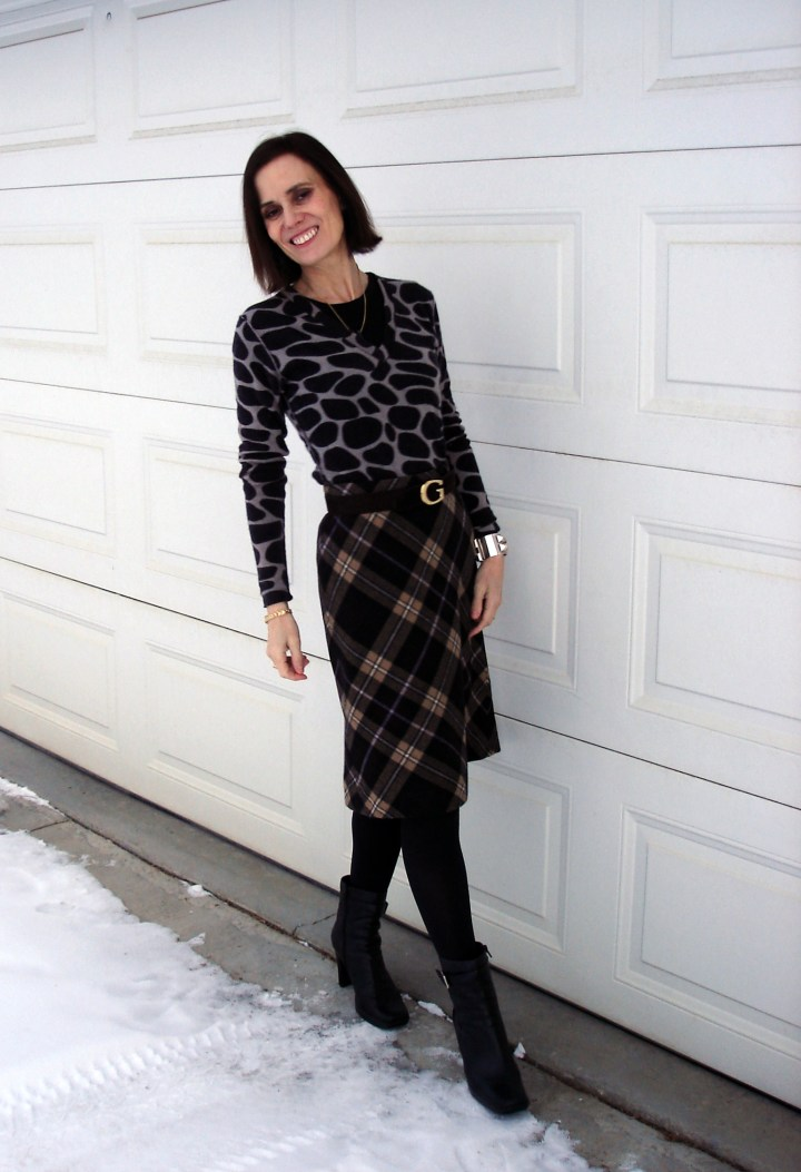 #styleover40 woman wearing a diagonal plaid A-line skirt with giraffe print sweater