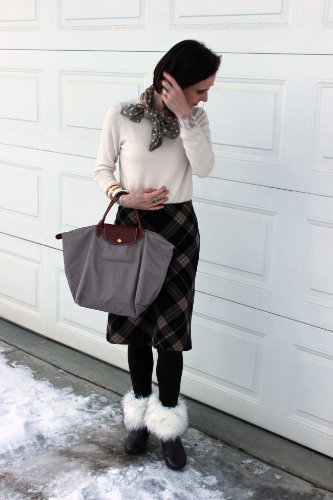 midlife blogger in all neutral outfit with skirt, sweater, polka dot scarf