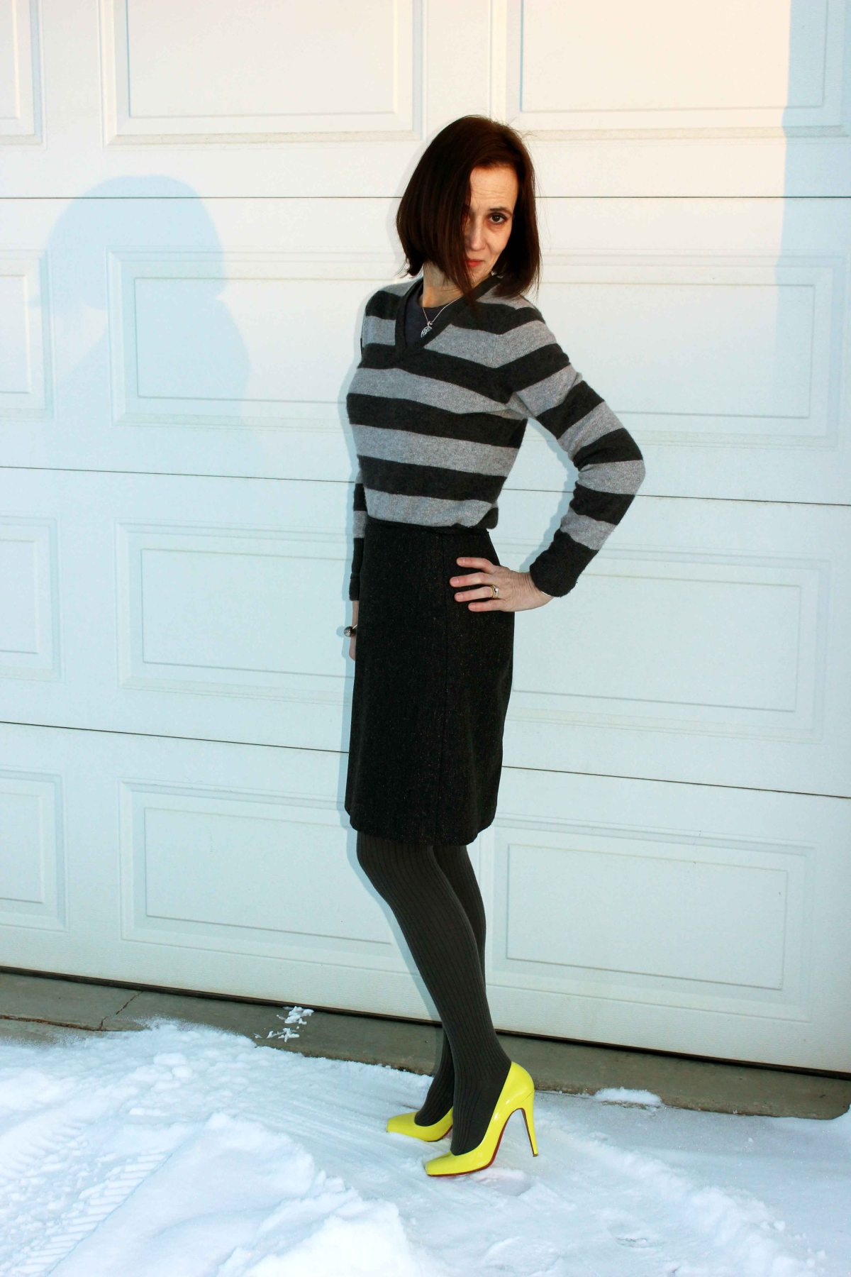 fashion blogger in monochromatic gray outfit with a pop of neon yellow