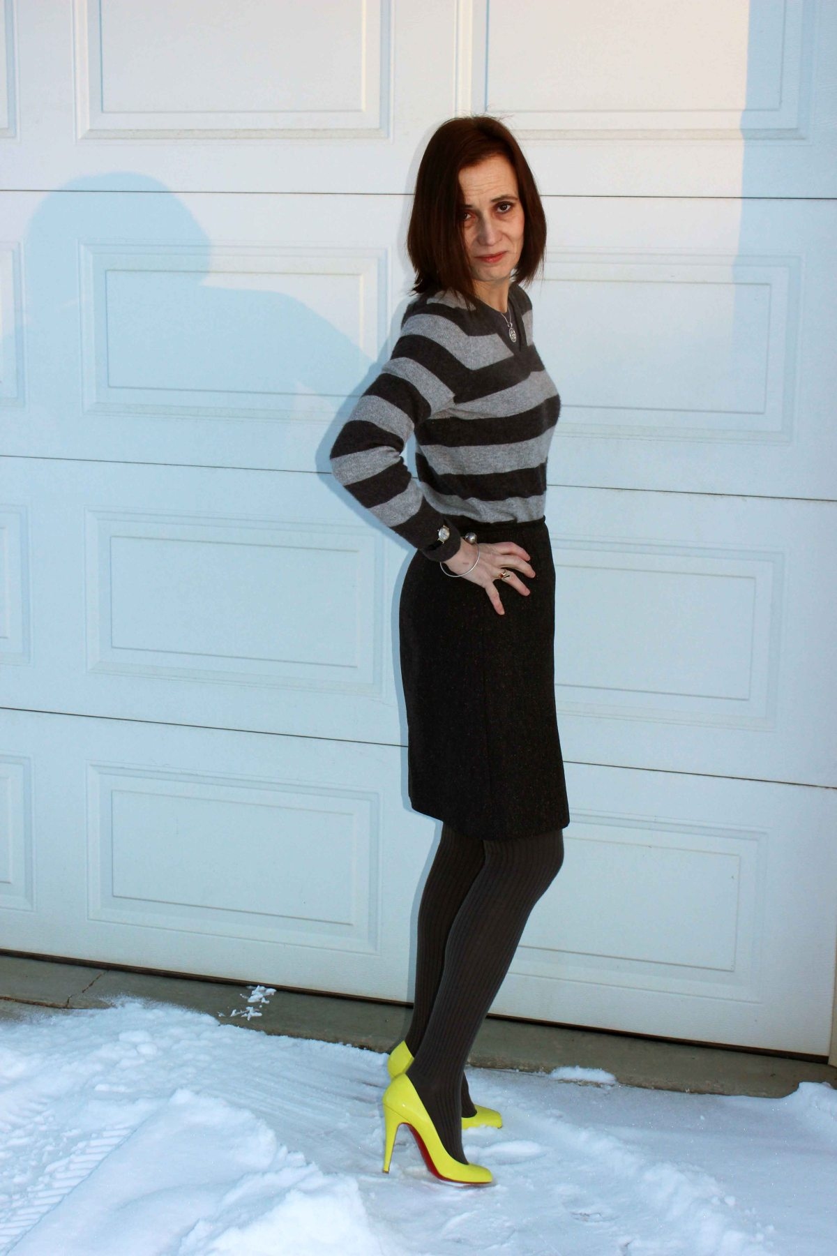 midlife style blogger donning neon shoes with a tweet skirt and striped cashmere sweater