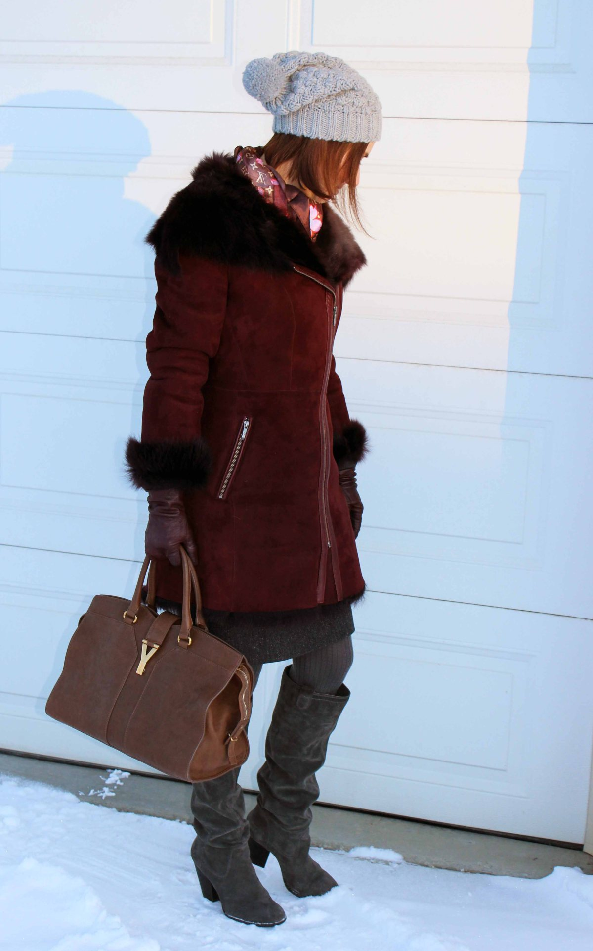 mature woman in burgundy motorcycle shearling coat, pom pom hat and boots