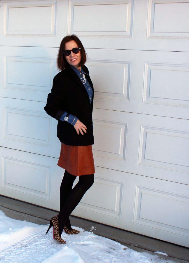 stylist in leo pumps, black blazer, tan skirt, black tights, denim shirt