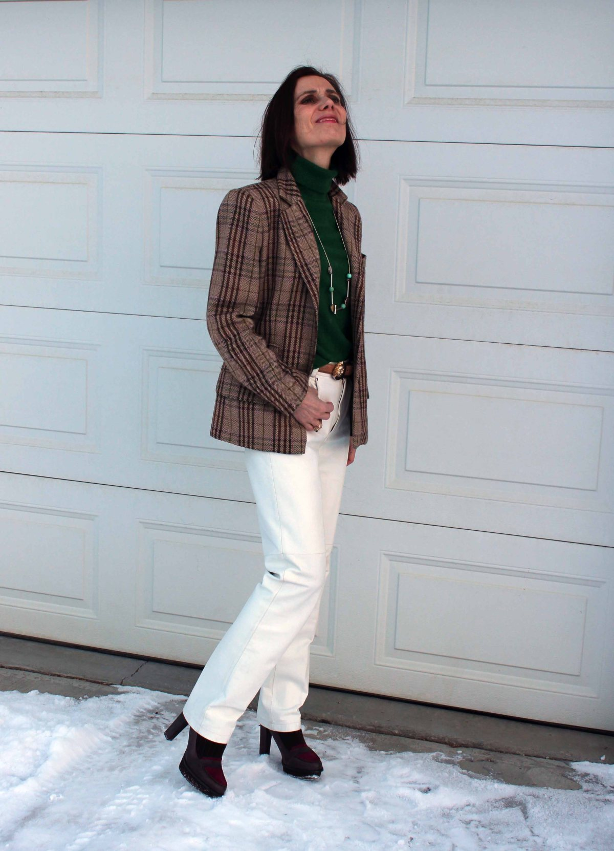 fashion blogger over 50 in casual posh work outfit with white pants and tartan blazer and green turtleneck cashmere sweater