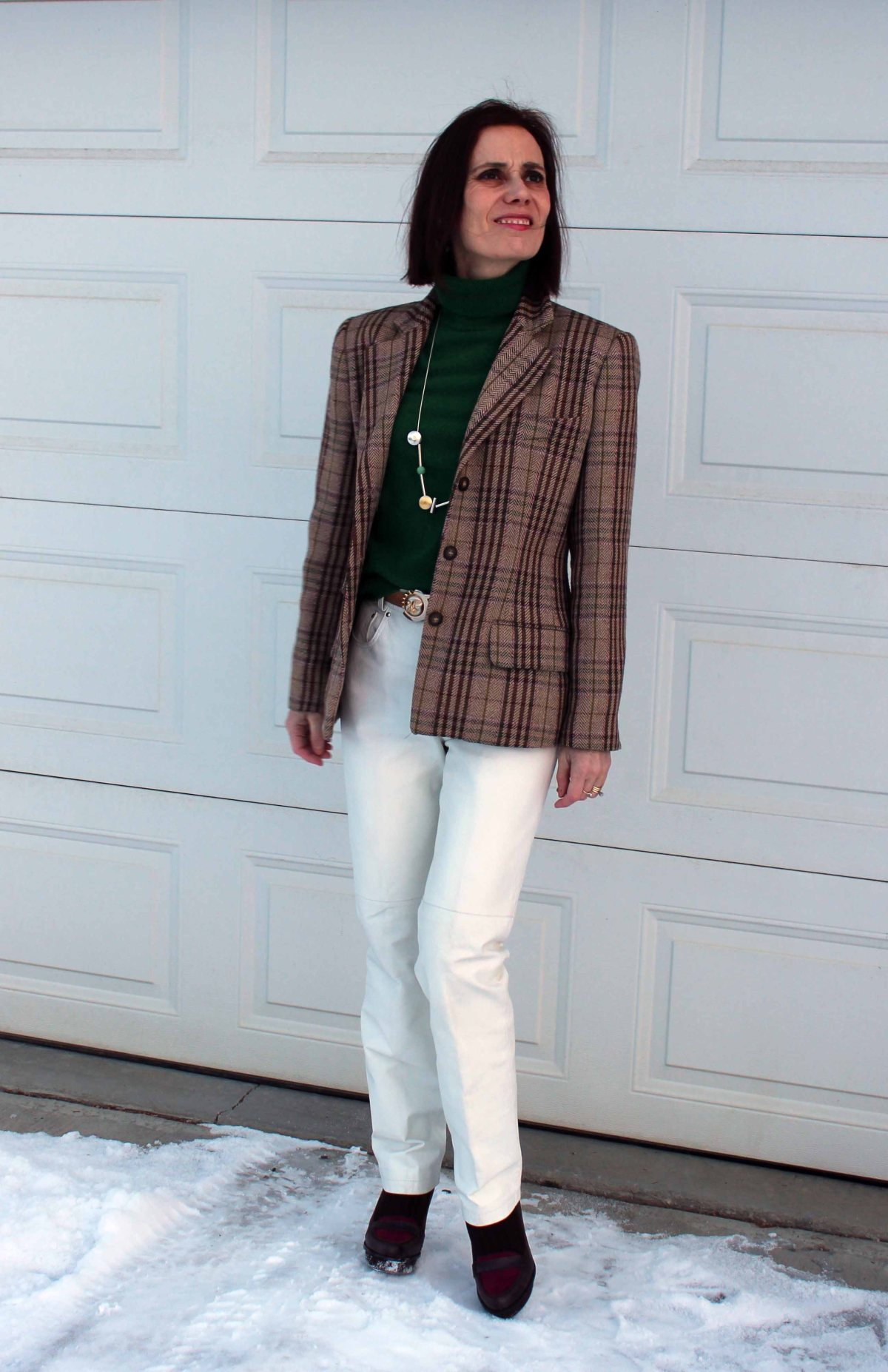 stylistn in white leather pants with tartan blazer and green sweater