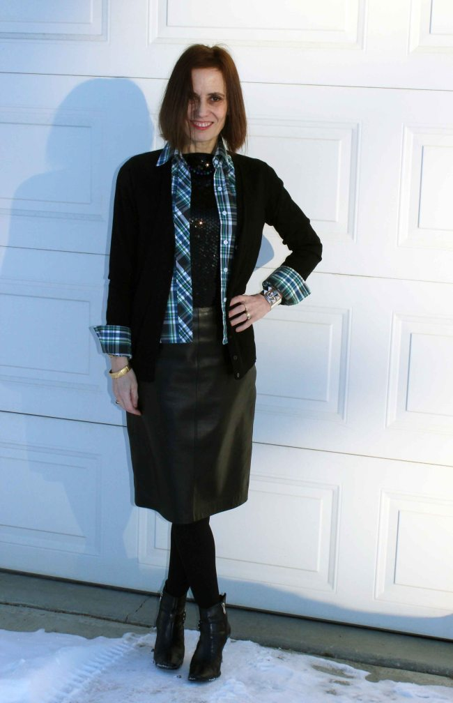 style book author standing in the shade with a casual work outfit with plaid and sequins