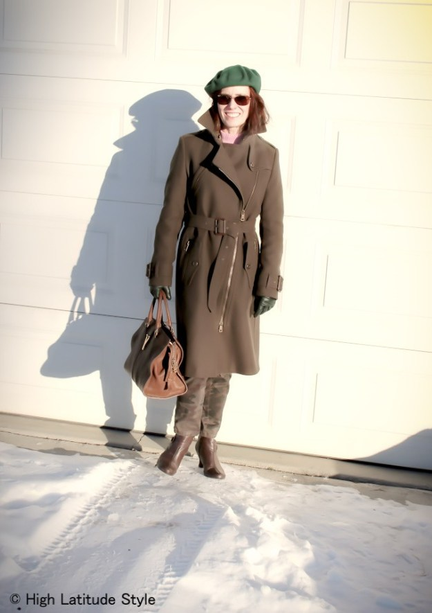 #styleover50 Women wearing a green beret and Burberry coat with camouflage pants