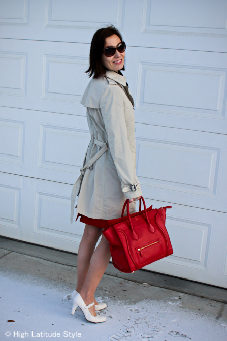 stylist in trench coat with red bag