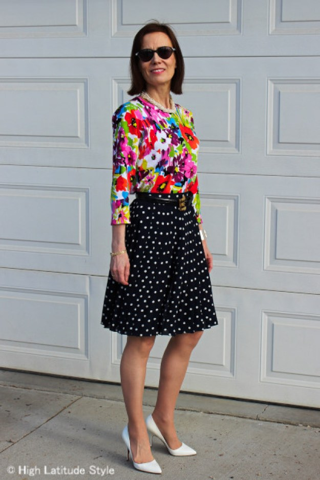 #fashionover50 woman in floral top with pleated polka dot skirt
