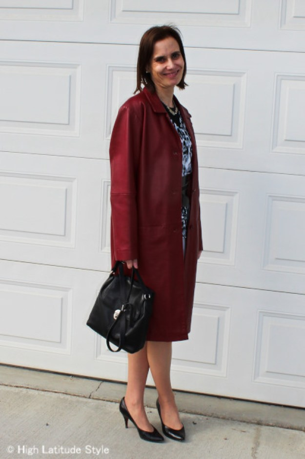 midlife woman in classic boxy rust leather coat with structured bag, snow leopard print jacket