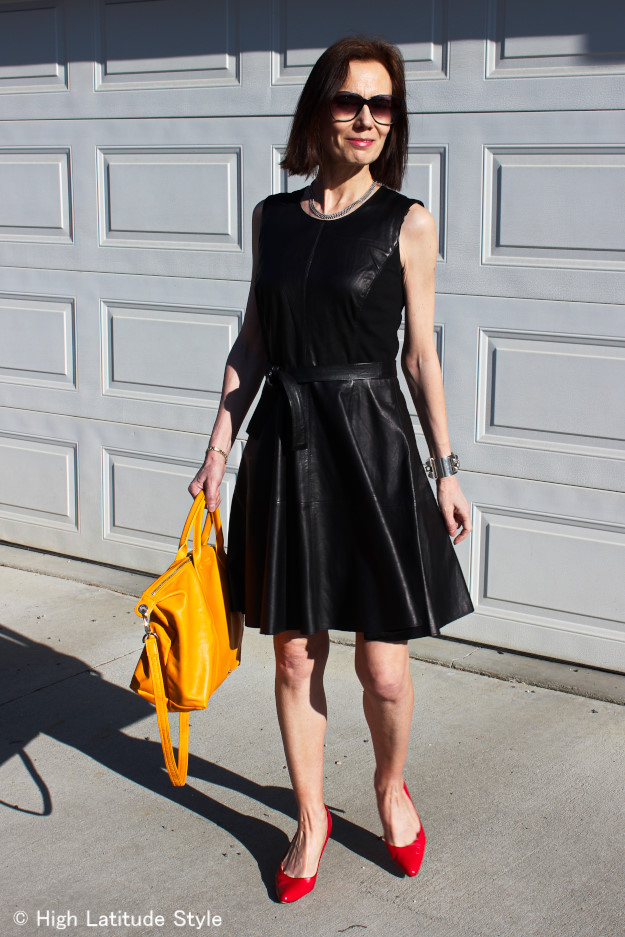leather lady in leather dress with red pumps and yellow bag