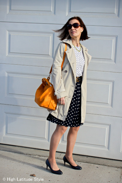 midlife woman wearing a trench with polka dot skirt