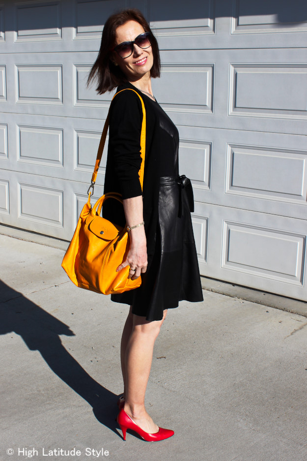#fashionover50 mature woman looking posh in a black Fit-and-flare Leather Dress and yellow and red pops of color