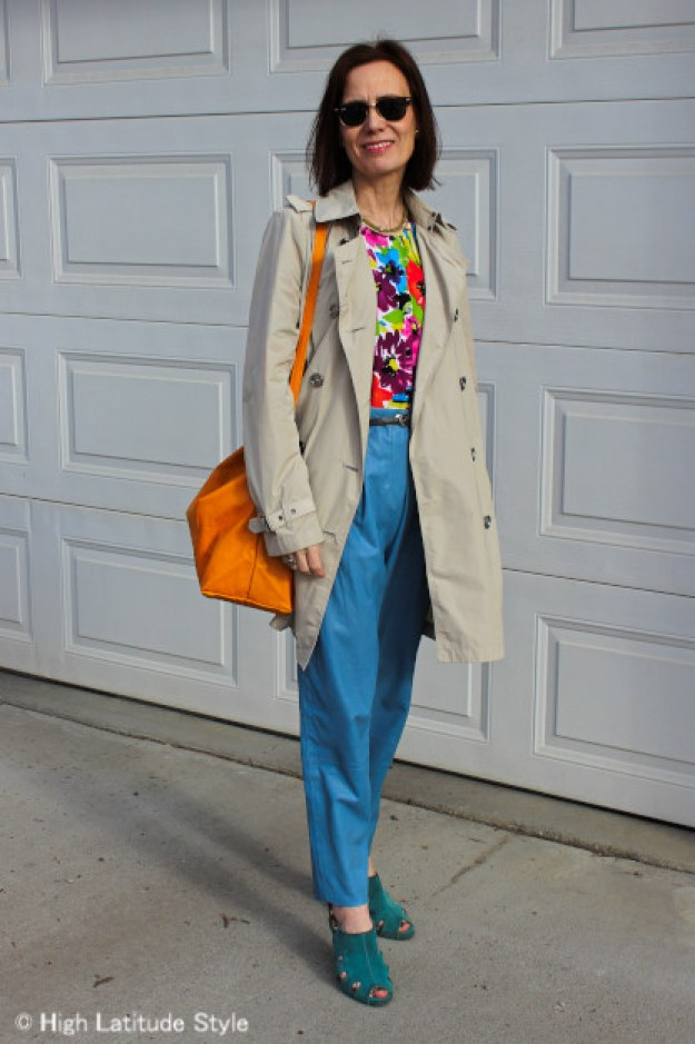 style book author in floral cardigan as top, rain coat and light blue leather pants