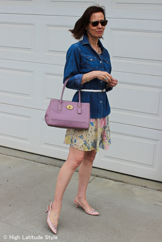 Alaskan style blogger in pastel floral skirt, chambray shirt, Chanel belt, Coach bag posing in the morning