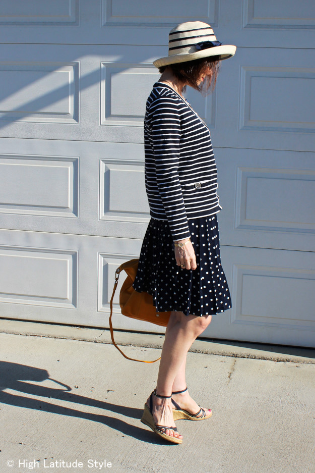 #fashionover50 mature woman in striped cardigan with polka dot pleated skirt and straw hat at High Latitude Style