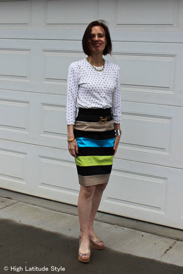 #fashionover40 woman in a work outfit with a polka dot top and a striped skirt