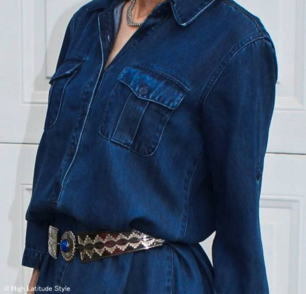 over 50 year old woman creating an awesome fall wardrobe outfit with a denim dress and ethnic belt