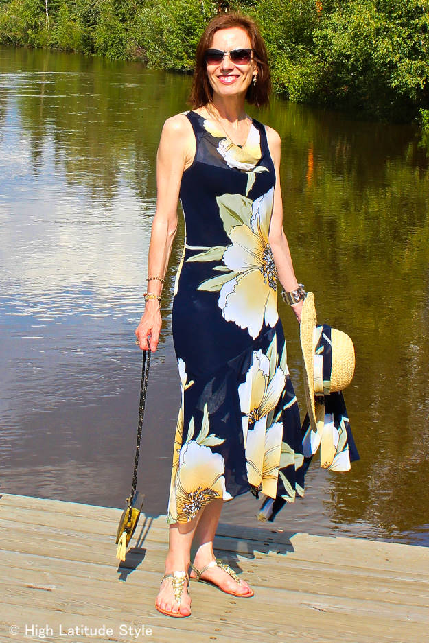 midlife woman in maxi dress with large floral print and wide brim hat