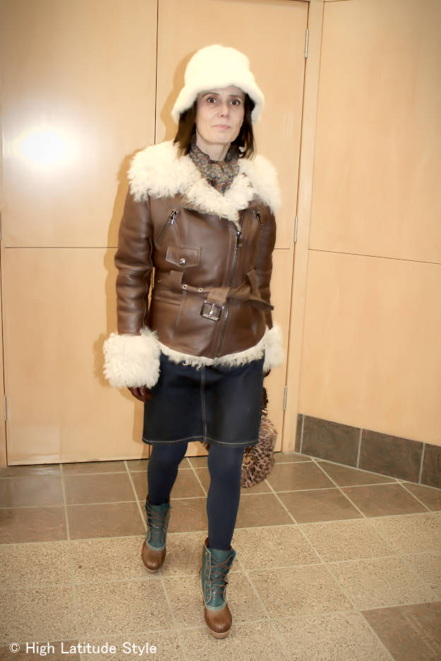#advancedstyle woman in Andrew Marc Shearling motorcycle jacket with denim skirt
