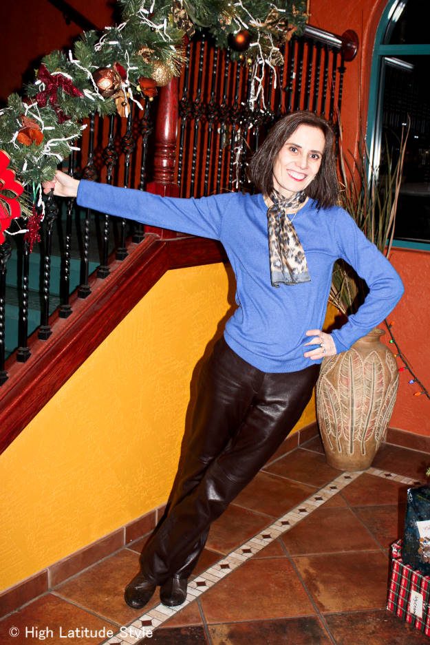 fashion blogger over 40 wearing leather pants and a statement color sweater with leopard print scarf