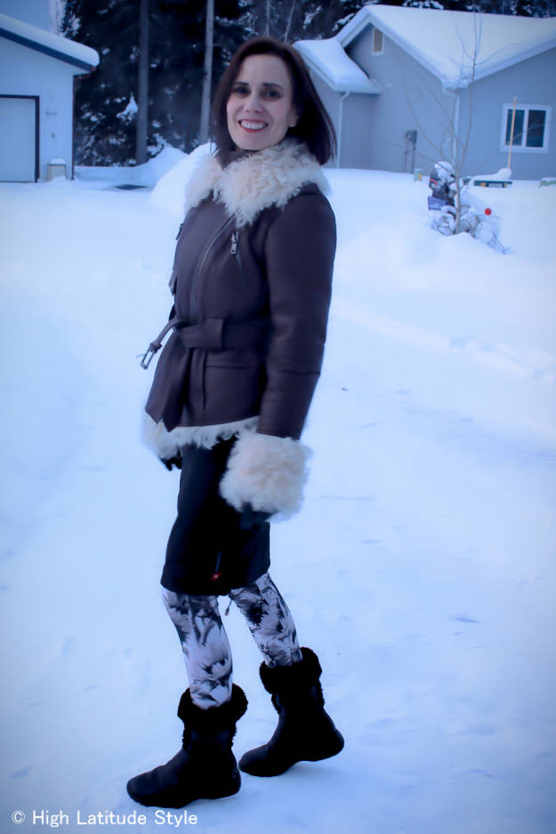 midlife style blogger in Alaska street chic with patterned leggings, thermal insulation skirt, shearling jacket and booties