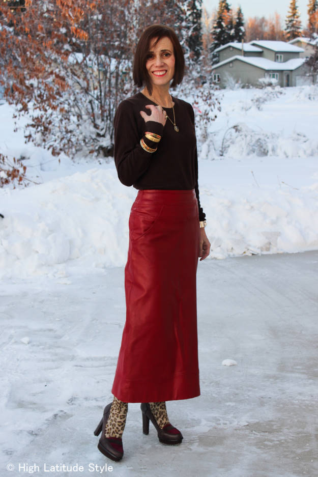 older woman in maxi leather skirt with sweater around equinox