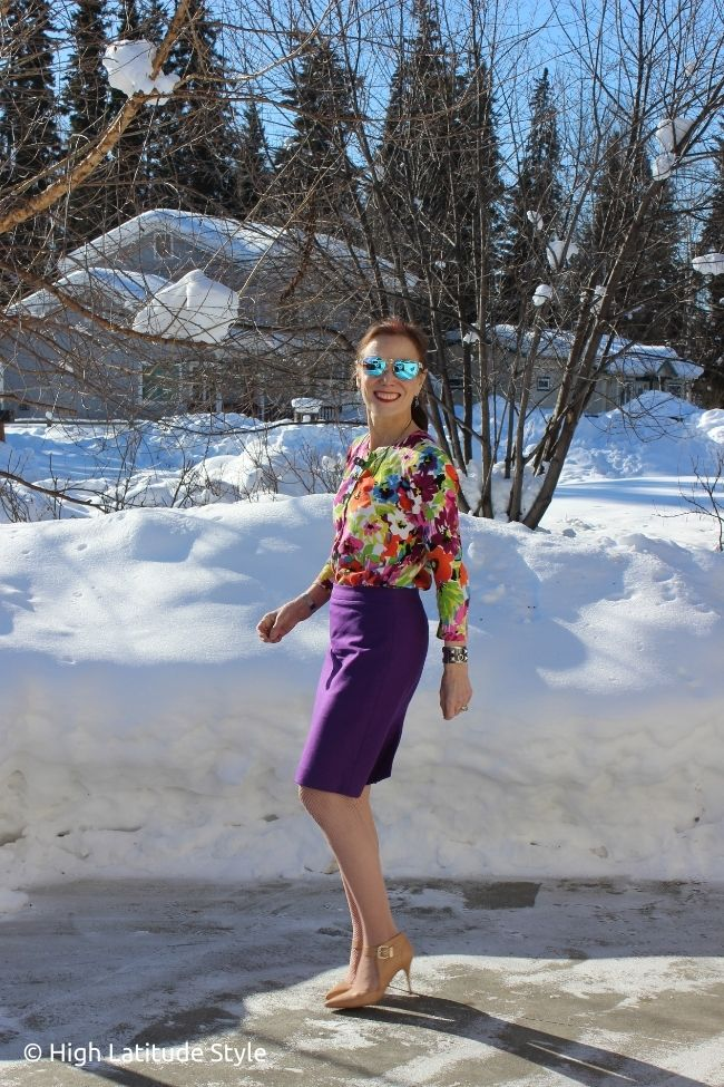 stylist in colorful Easter outfit with floral top purple skirt nude pumps