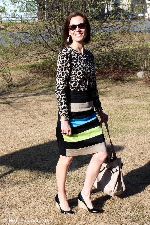 fashion blogger over 50 in a work outfit with leopard print top and striped skirt