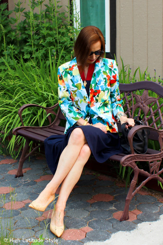 #chicover50 blogger sitting on a bench in a floral blazer with fit-and-flare dress