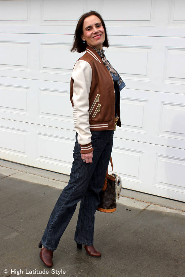 fashion blogger Nicole donning a classic baseball jacket with jeans look